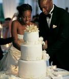Model Christopher Collins in a black tuxedo cuts wedding cake with his bride in a Reem Acra gown