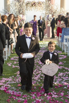 Two latin boys walking down petal-covered aisle