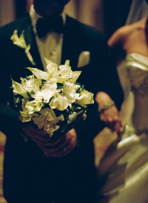 Groom carrying his bride's ivory bouquet