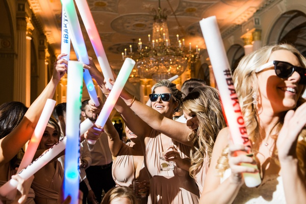 Glow stick and sunglasses party favors on dance floor with wedding hashtag