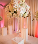 indoor ceremony, floral arrangements with orchids, hydrangeas, roses in crystal vase on white pillar