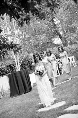Black and white photo of bride in a Claire Pettibone gown walking with bridesmaids