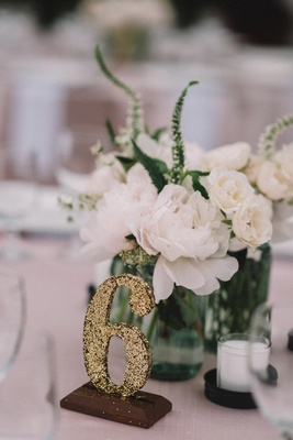 White peony mason jar centerpiece with DIY gold glitter table number