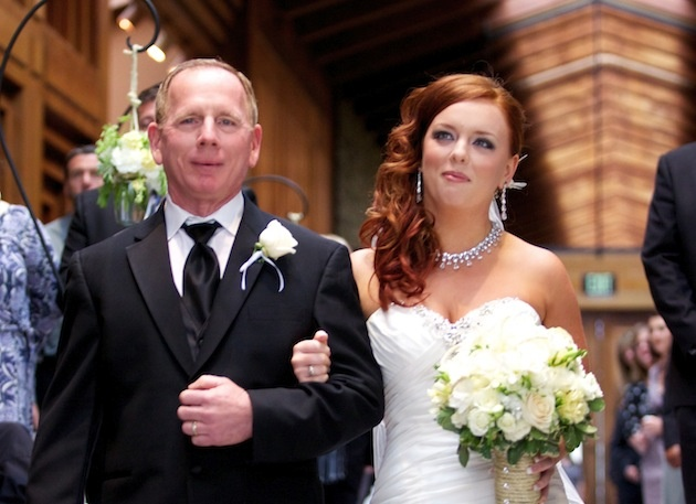 Red hair bride walks down aisle with father of bride