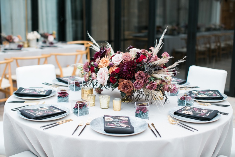 round table with centerpiece of burgundy and mauve roses with pampas grass