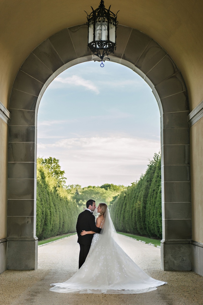 Bride and groom under tall archway at Oheka Castle gardens cyprus trees clouds sky