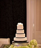 black and white wedding cake with white tiers, black ribbon details, and white cake topper