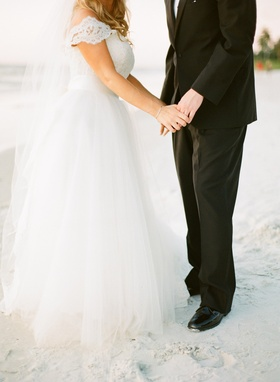 Bride in a Monique Lhuillier gown with tulle skirt and lace bodice with groom in black tuxedo