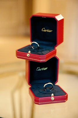 Cartier wedding bands in red boxes for bride and groom