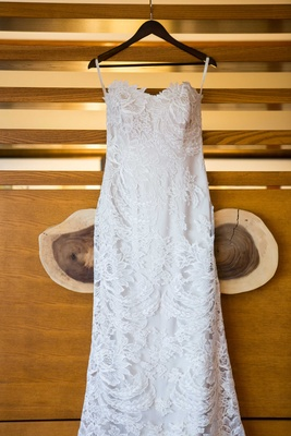 white lace fit and flare gown with sweetheart neckline hanging up