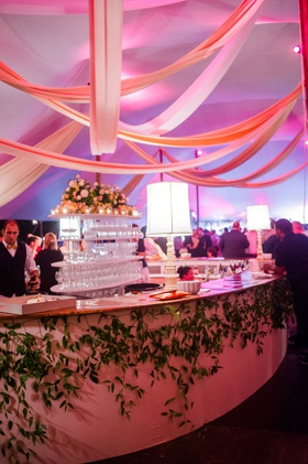 wedding reception tent after party lamps on bar with greenery purple violet pink lighting on drapery