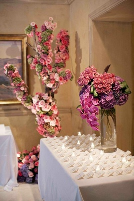 Pink and purple floral arrangements on white table