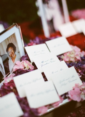 Wedding escort cards with calligraphy on top of pink and purple flowers next to old family photos