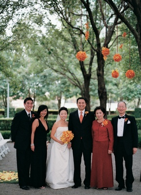 Bride in strapless dress and groom in black tuxedo and orange tie with family