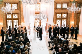 Wedding ceremony with tall white drapery chandeliers bridesmen bridesmaids and groomsmen rustic