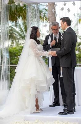 bride in custom rivini high-low wedding dress, groom in tuxedo, minister officiates