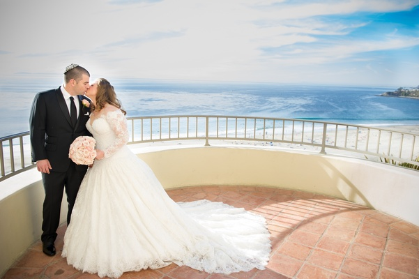 Bride and groom kiss with Pacific ocean backdrop