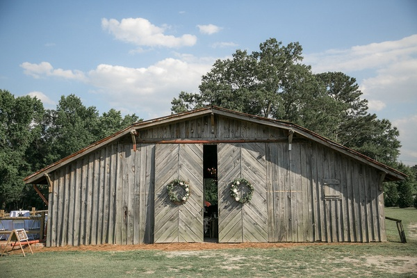 Wedding reception barn venue sliding barn doors with wreaths and old wood siding north carolina