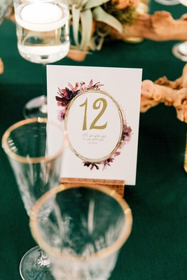 wedding reception emerald green velvet linen purple flower design gold table number card