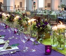 Purple linen with green runner and low flower centerpieces
