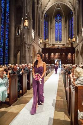 Bridesmaid wearing strapless purple dress down aisle