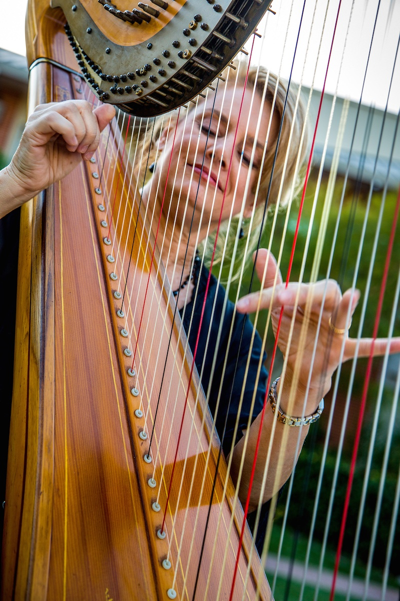 Blonde woman plucking Harp strings at ceremony