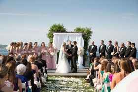 Bride and groom at white ceremony structure on coast