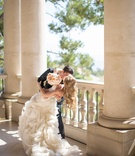 Groom kissing bride in Vera Wang gown
