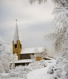 Snow-covered road, trees, and church