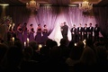 Wedding ceremony in a ballroom with purple lighting and candlelight