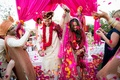 Bride and groom recessional at Indian wedding with vibrant magenta and yellow flower petal toss