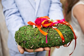 ring bearer pillow covered with moss hot pink and orange rose flowers and ribbons