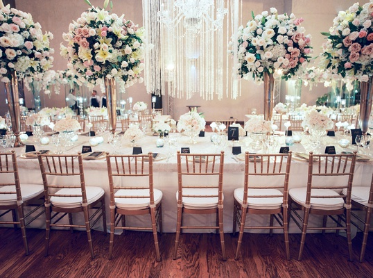 long wedding reception table with gold chairs high and low centerpieces greenery orchid rose flowers