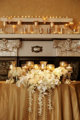 Fireplace mantle with candles and gold goblets
