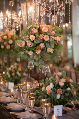 Rustic elegant wedding reception table with high low rustic centerpiece and elegant chandeliers gold