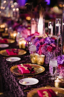 Wedding reception table long purple linens fuchsia pink flowers and napkins gold candles floating