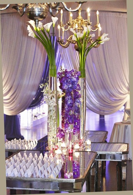 White escort cards on mirror table with tall flower arrangements