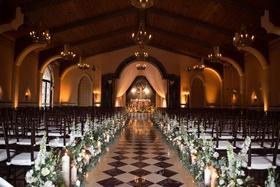 Grand del mar wedding ceremony diamond pattern tiles church feel wood chairs rustic elegant flowers