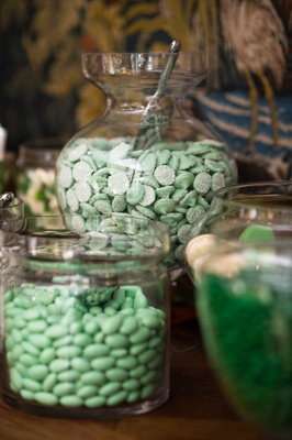Mint green candy and dessert bar in apothecary jars at wedding
