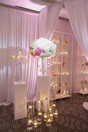 white shelves with floating candles, candelabra, white and pink flowers