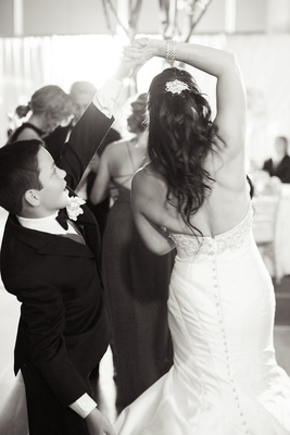 brides son spins mom around black tuxedo trumpet wedding gown having fun