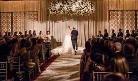 wedding guests at ceremony jewish wedding hanging chuppah flowers orchid lily rose hydrangea stock