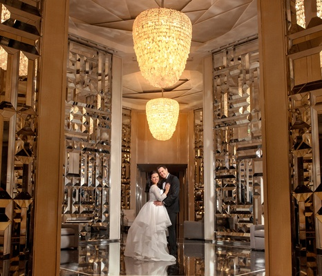 bride in rivini hi-low gown with lace long sleeves, groom in tux, metallic textured walls