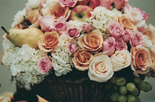 Rose, pear, and apple centerpiece in urn