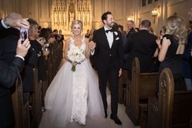 bride and groom smiling at wedding guests in pews at catholic church ceremony overskirt wedding gown
