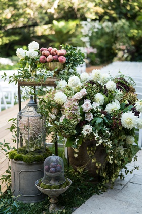 wedding ceremony wood aisle entrance with lantern wood table peach fruits white dahlia rose