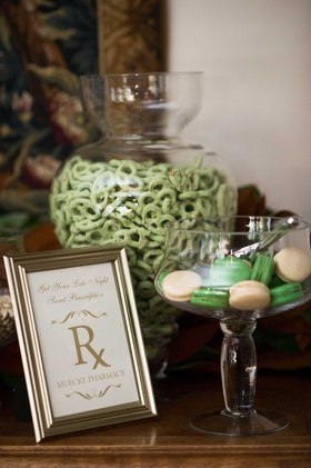 Dessert station with green chocolate pretzels and macarons in apothecary jars with Rx pharmacy sign