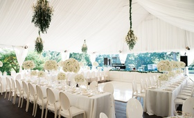 tented wedding reception, white drapery, white linens and chairs, ivory florals, greenery accents