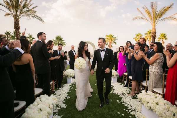 Bride in Galia Lahav wedding dress holding groom's hand and bouquet while walking down grass aisle