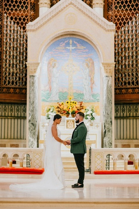 bride and groom holding hands traditional church wedding miami altar white flowers greenery